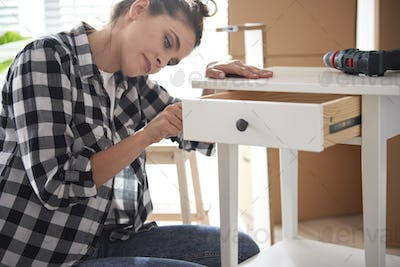 Young woman renovating a night table