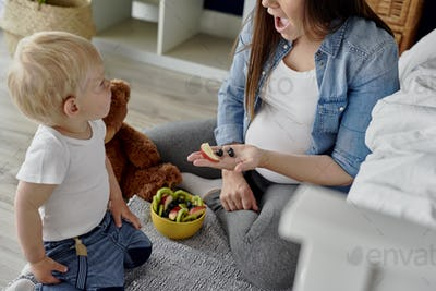 Mother having a fruity snack for her toddler baby