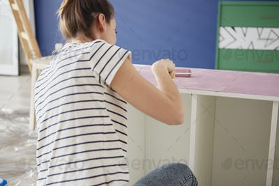 Young woman repainting old furnitures