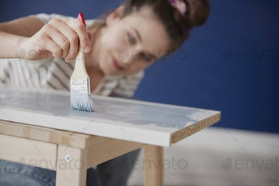 Close up of young woman repainting old furniture