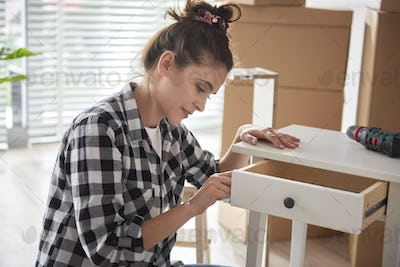 Focus woman renovating a night table