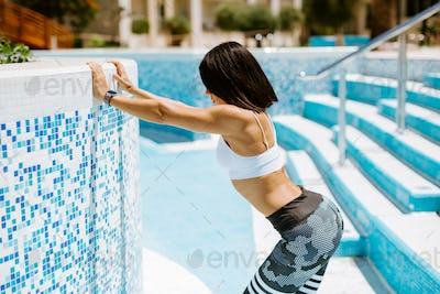sexy athletic woman stretching exercises and wearing fitness watch