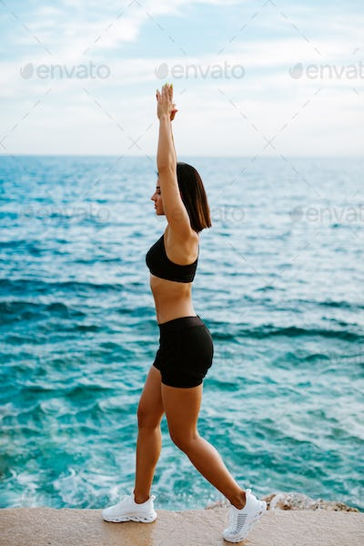 sexy athletic woman stretching exercises outdoors with sea view