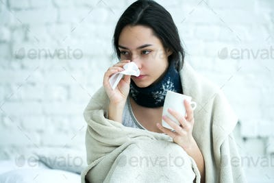 Young woman sick with temperature drinks hot