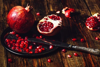 Whole and Opened Pomegranates on Metal Plate.