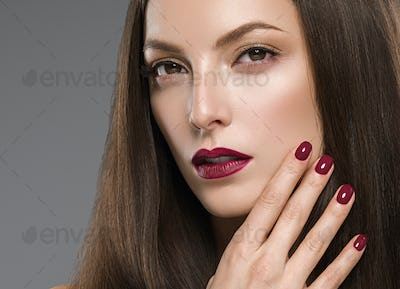 Beautiful brunette woman red lips manicure with long hair natural makeup face closeup. Studio