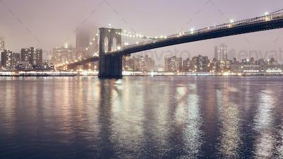 Brooklyn Bridge at a foggy night, New York.