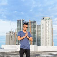 Full body shot of young handsome multi ethnic man with sunglasses against view of the city
