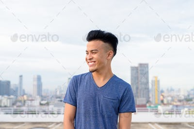 Happy young handsome multi ethnic man thinking against view of the city