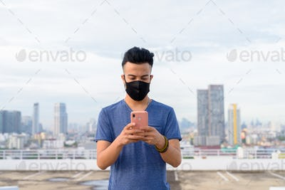 Young multi ethnic man with mask using phone against view of the city