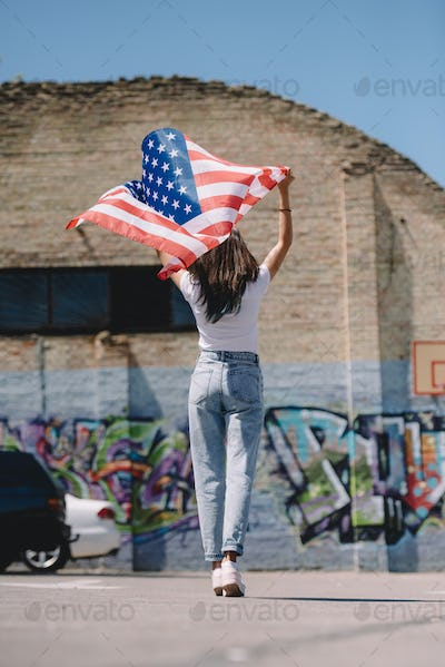 Back View of Woman With American Flag in Hands Standing on Street,4th July Holiday Concept