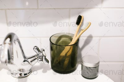 Plastic free bathroom items. Eco natural bamboo toothbrushes in glass
