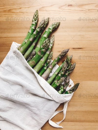 Reusable eco friendly bag with fresh asparagus on wooden table, flat lay.