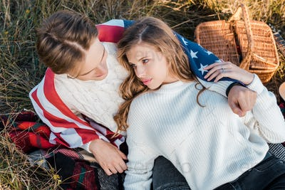 Young Couple With American Flag Resting on Rural Meadow,Independence Day Concept