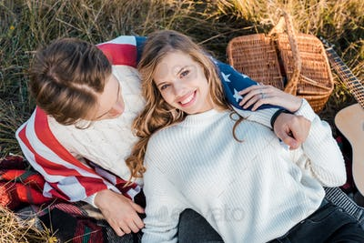 Attractive Couple With American Flag Relaxing on Grass,Independence Day Concept