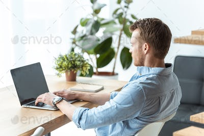 Selective Focus of Young Businessman Working on Laptop With Blank Screen at Table in Office