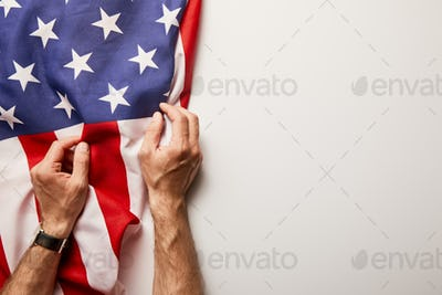 Cropped View of Man Holding American Flag on White Background With Copy Space
