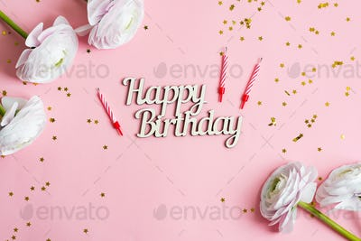 Festive backdrop from bright stars decoration, candles for cake and text Happy Birthday , ranunculus