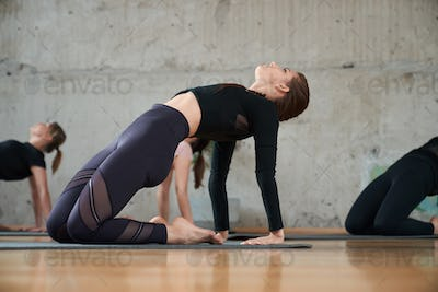 Young woman practicing yoga in hall