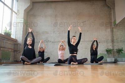 Group of women sitting in lotus pose in hall