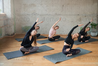 Group of women stretching in lotus pose in hall