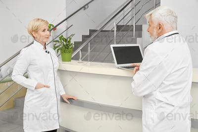 Female doctor talking with coworker near hospital reception