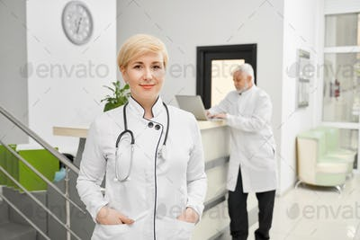 Female doctor keeping hands in pockets