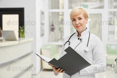 Female doctor in coat holding folder