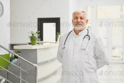 Eldery doctor in lab coat ppsoing near reception
