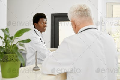 African and caucasian doctors on reception