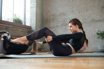 Fit women practicing yoga in hall