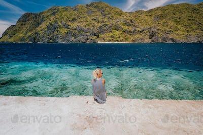 Tourist female rear view sitting pier edge on Matinloc island on hoping tour C. El Nido, Palawan