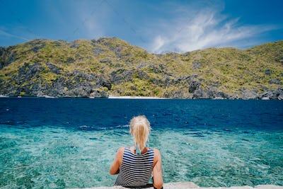 Tourist female rear view sitting on Matinloc dock pier enjoying tapiutan strait on island hoping