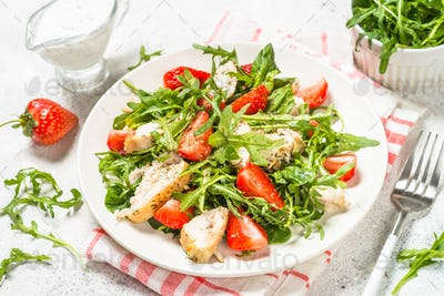 Green salad with chicken, strawberry and arugula