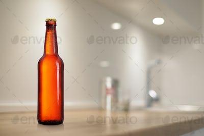 Brown beer bottle on kitchen table. Mock-up design presentation.