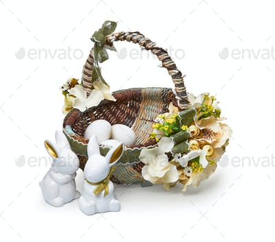 Easter basket from a flower arrangement and a rabbits on white background