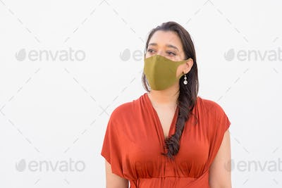 Young Indian woman wearing mask and thinking against white background