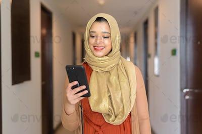 Happy young beautiful Indian Muslim woman using phone in the corridor