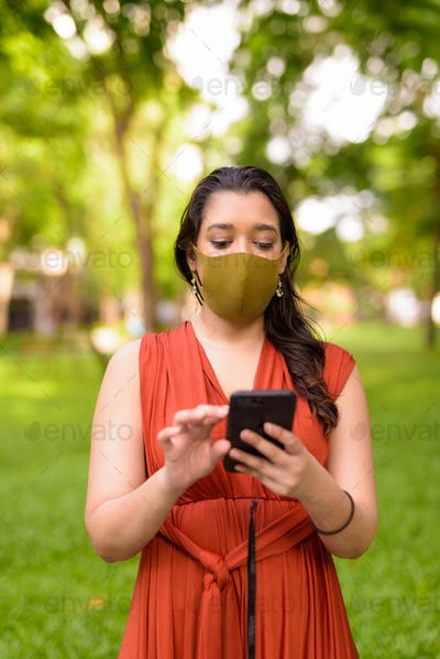 Young Indian woman with mask using phone at the park outdoors