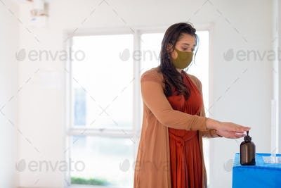 Young Indian woman with mask using hand sanitizer as proper hygiene etiquette indoors