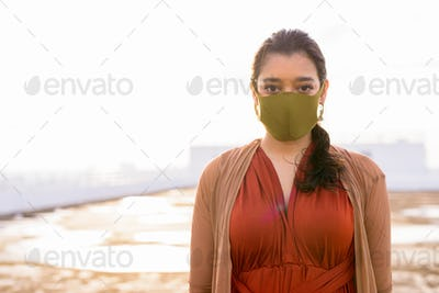 Young Indian woman with mask for protection from corona virus outbreak at rooftop of the building