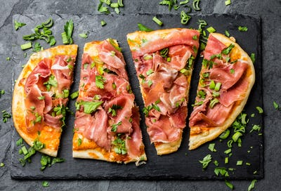 Naan pizza with ham serrano on slate board