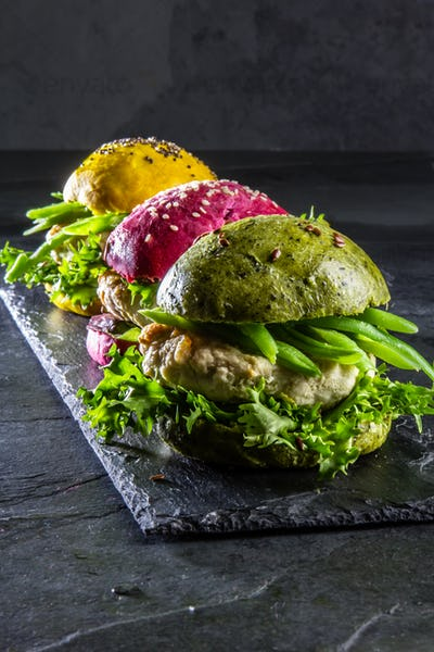 Colored green, yellow and purple burgers on slate board, slate background