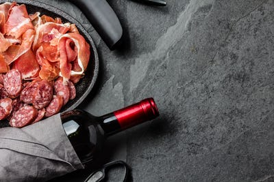 Spanish ham serrano, salami and bottle of red wine on slate