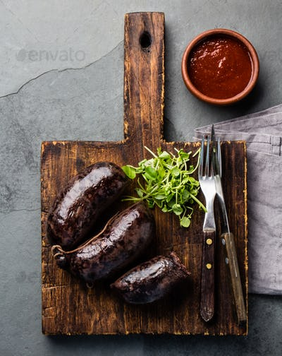 Bloody sausages - prieta on wooden board with chili sauce, top view