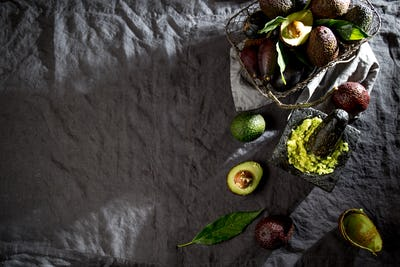 Avocado. Guacamole. Mexican guacamole sauce in stone mortar, full basket with avocado, half of
