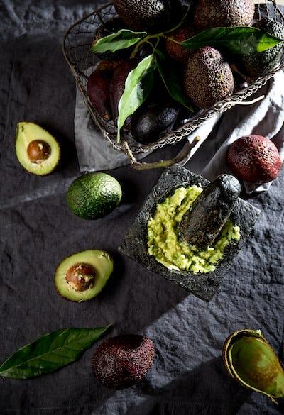 Mexican guacamole sauce in stone mortar, full basket with avocado