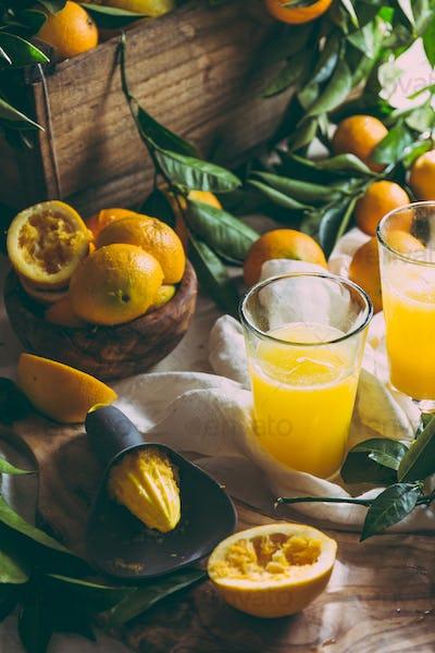 Orange juice, full box of orange fruits ant orange tree branches on table
