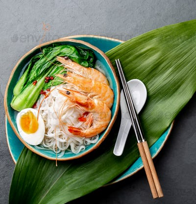 Rice noodles with Shrimps, Egg, Pok choy cabbage in blue bowl, gray background. Top view