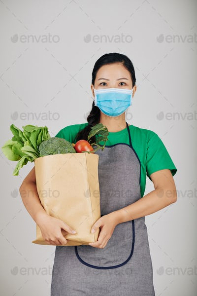 Supermarket worker with paper package